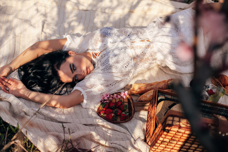 fashion outdoor photo of beautiful sensual woman with dark hair in elegant dress having romantic picnic among flowering peach trees in garden