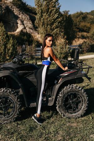 fashion photo of beautiful woman with dark hair in elegant sportive suit posing in quad bike Reklamní fotografie