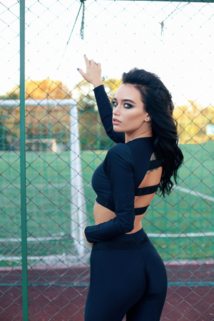 fashion photo of beautiful woman with dark hair in elegant sportive suit posing near outdoor playground