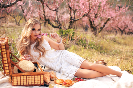 fashion outdoor photo of beautiful girl with blond hair in elegant dress having romantic picnic among flowering peach trees in garden Banque d'images - 121940900