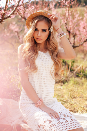 fashion outdoor photo of beautiful girl with blond hair in elegant dress having romantic picnic among flowering peach trees in garden