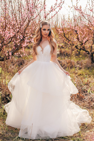 fashion outdoor photo of beautiful  woman with blond hair in elegant wedding dress posing among flowering peach trees in garden Imagens