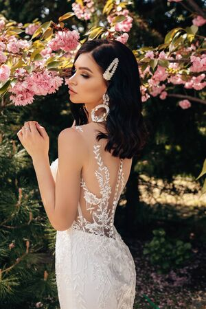 fashion outdoor photo of beautiful woman with dark hair in luxurious wedding dresses with accessories posing in garden with blossoming sakura trees