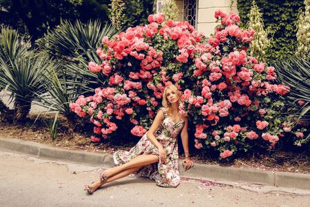 fashion outdoor photo of beautiful sensual woman with blond hair in elegant dress posing near roses bushes in summer garden Stock fotó - 129299990