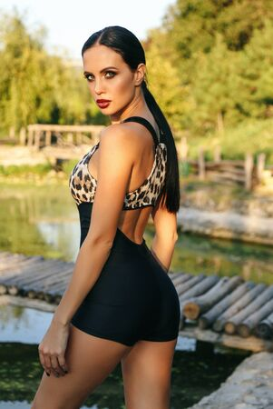 fashion photo of beautiful woman with dark hair in elegant sportive suit posing near lake in summer park