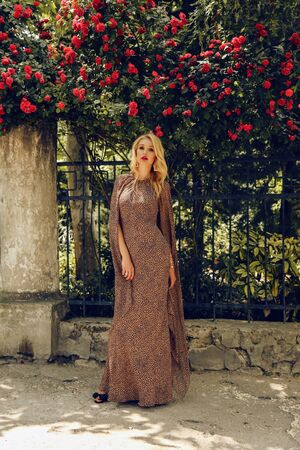fashion outdoor photo of beautiful sensual woman with blond hair in elegant dress posing near roses bushes in summer garden