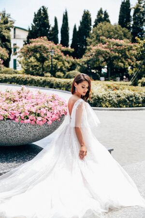 fashion outdoor photo of beautiful woman with dark hair in luxurious wedding dress posing in summer park near blossoming flowers