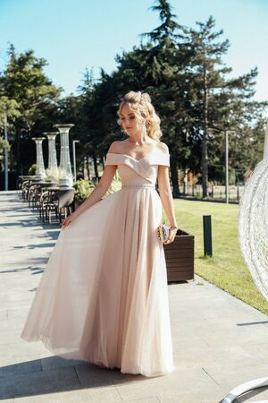 fashion outdoor photo of beautiful young woman with blond curly hair in luxurious evening dress and accessories posing in summer park Stock fotó - 129004985