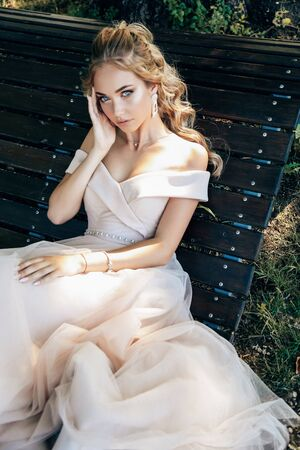 fashion outdoor photo of beautiful young woman with blond curly hair in luxurious evening dress and accessories posing in summer park