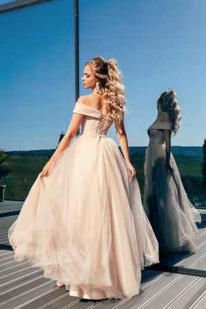 fashion outdoor photo of beautiful young woman with blond curly hair in luxurious evening dress and accessories posing near mirror window Stock fotó - 129004716