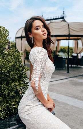 fashion outdoor photo of beautiful woman with dark hair in luxurious wedding dress posing in summer park Stock fotó - 129300204