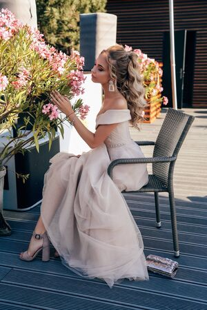 fashion outdoor photo of beautiful young woman with blond curly hair in luxurious evening dress and accessories posing in summer park Stock fotó - 129004710