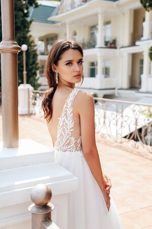 fashion outdoor photo of beautiful woman with dark hair in luxurious wedding dress posing in summer park