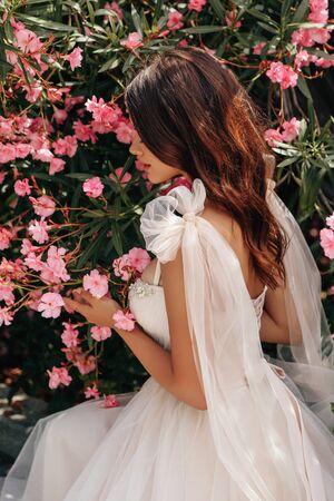 fashion outdoor photo of beautiful woman with dark hair in luxurious wedding dress posing near flowering oleander bush in summer park