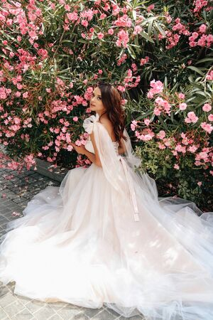 fashion outdoor photo of beautiful woman with dark hair in luxurious wedding dress posing near flowering oleander bush in summer park Stock fotó - 129300223