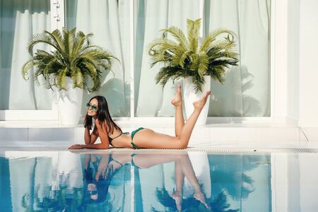 fashion outdoor photo of beautiful sensual woman with dark hair in elegant swimming suit and beach tunic posing near swimming pool at white villa