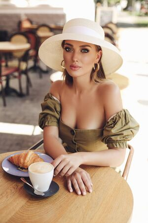 fashion outdoor photo of beautiful girl with blond hair in elegant clothes and accessories posing in cafe Stock fotó
