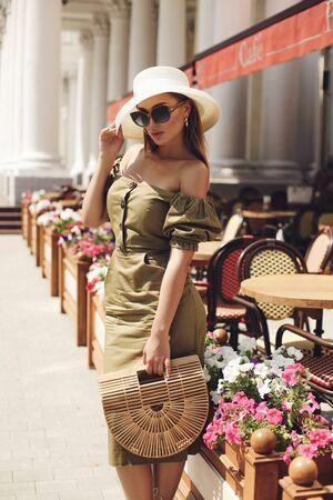 fashion outdoor photo of beautiful girl with blond hair in elegant clothes and accessories posing in cafe Stock fotó - 129005316