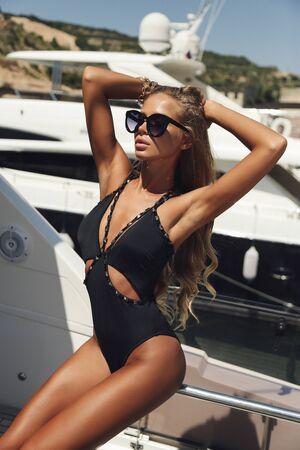 foto di moda di una bella donna con i capelli biondi in un elegante costume da bagno che si rilassa su uno yacht di lusso Archivio Fotografico