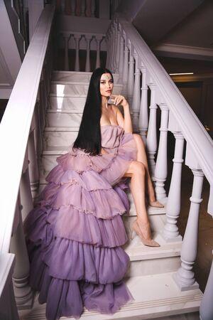 fashion interior photo of beautiful woman with dark hair in elegant dress and extravagant make up celebrating Halloween