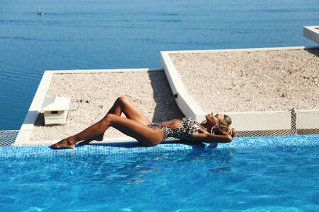 fashion outdoor photo of beautiful woman with blond hair in elegant swimming suit posing near open air swimming pool