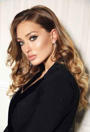 fashion studio photo of beautiful sensual woman with blond curly hair in elegant clothes