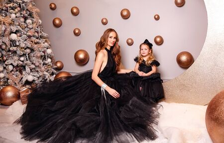 fashion interior photo of beautiful woman with red hair in luxurious dress posing with her little cute daughter near Christmas tree in decorated room