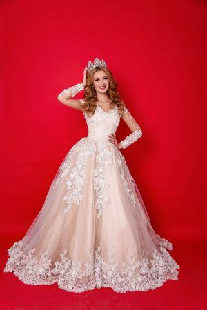 Modefoto einer schönen Frau mit blonden Haaren im luxuriösen Hochzeitskleid mit eleganter Krone, die im Studio posiert