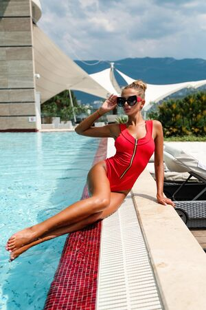 fashion outdoor photo of beautiful woman with blond hair in elegant swimming suit posing near swimming pool
