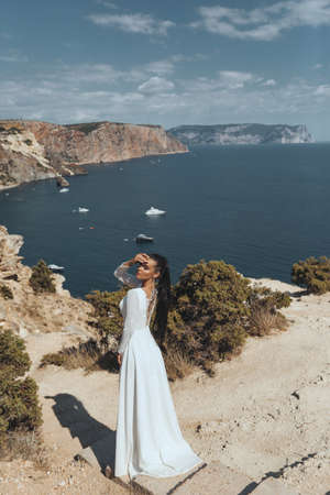 fashion outdoor photo of beautiful woman with dark hair in luxurious wedding dress and accessories posing in beautiful landscape Stock fotó