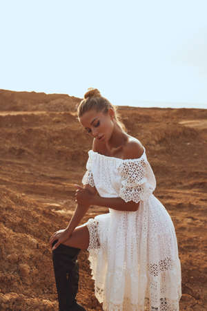 fashion photo of beautiful sexy woman with blond hair in elegant dress and accessories posing in desert