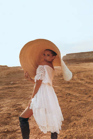 fashion photo of beautiful sexy woman with blond hair in elegant dress and big straw hat posing in desert