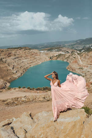 fashion outdoor photo of beautiful sexy woman with blond hair in luxurious dress posing in beautiful landscape with lake view