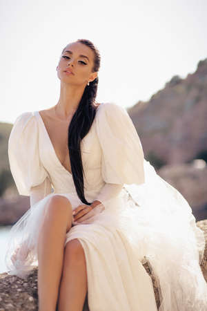 fashion photo of beautiful woman with dark hair in luxurious white dress posing in beautiful landscape with sea view Stock fotó