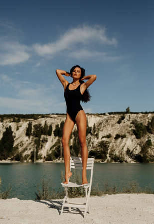 fashion outdoor photo of beautiful sexy woman with dark hair in swimming clothes posing with chair near lake and mountains