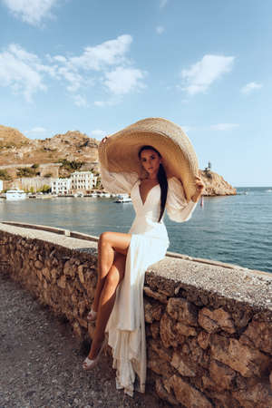 fashion photo of beautiful woman with dark hair in luxurious white dress and hat posing in beautiful landscape with sea view Stock fotó