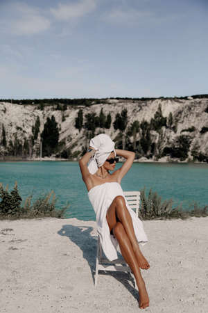 fashion outdoor photo of beautiful sexy woman with dark hair with bath towels on body and head posing near lake and mountains Stock fotó