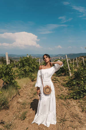 fashion outdoor photo of beautiful sexy woman with dark hair in elegant clothes and accessories posing in vineyard