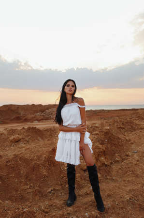 fashion outdoor photo of beautiful sexy woman with dark hair in elegant clothes and accessories posing in desert Stock fotó