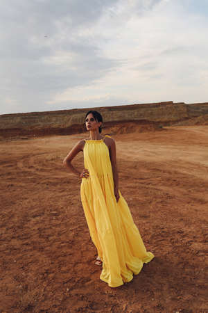 fashion outdoor photo of beautiful sexy woman with dark hair in elegant dress and accessories posing in desert Stock fotó