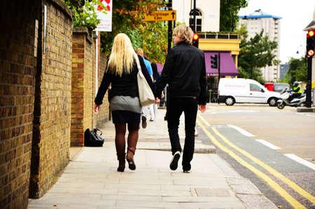 Ein junges Paar ist auf der Straße ging, die Hände halten.