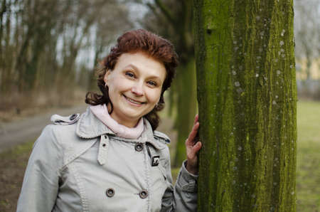 A happy beautiful young woman is smiling in a park, leaning on a tree    Stock Photo