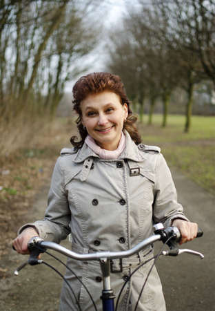 A happy beautiful young woman is having fun riding a bicycle  Stock Photo