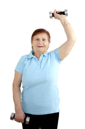 A mature woman is doing a workout with dumbbells and is having fun