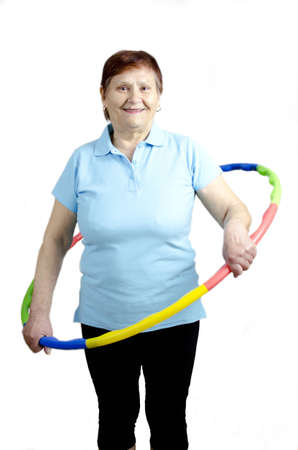 A mature woman is doing a workout with a hula hoop and is having fun