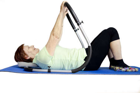 A mature woman is doing sit-ups and is having fun