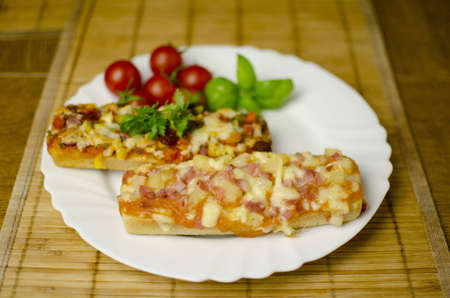 2 baguette pizzas are placed on a white plate with tomatoes and parsley in the background. Shallow depth of the field. Stock Photo