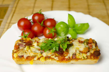 A close-up of baguette pizza on a white plate with vegetables in the background. Shallow depth of the field.