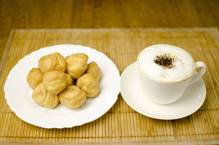 A cup of coffee and a plate full of cream puffs are on the table. Shallow depth of the field.