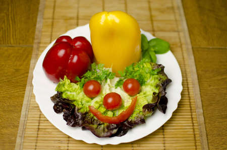 Tomatoes, peppers, salad are well decorated on a white plate. Shallow depth of the field. Stock Photo